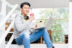 Szczęśliwy młody Azjatycki pracownik używa laptop w nowożytnym biurze zdjęcia royalty free