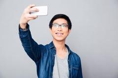 Szczęśliwy młody azjatykci mężczyzna robi selfie fotografii Obrazy Stock