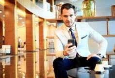 Szczęśliwy młody biznesmena obsiadanie relaksujący na kanapie przy hotelu kuluarowym używa smartphone Zdjęcie Royalty Free