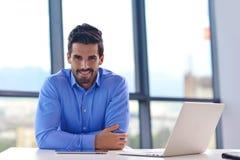 Szczęśliwy młody biznesowy mężczyzna przy biurem Zdjęcie Royalty Free