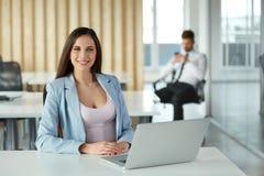 Szczęśliwy Młody bizneswoman przy biurem Obrazy Royalty Free