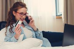 Szczęśliwy młody bizneswoman używa pastylka komputer osobistego w pokoju hotelowym Z kredytową kartą online zakupy Obraz Royalty Free