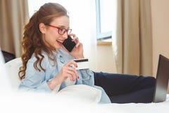 Szczęśliwy młody bizneswoman używa pastylka komputer osobistego w pokoju hotelowym Z kredytową kartą online zakupy Fotografia Royalty Free