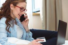 Szczęśliwy młody bizneswoman używa pastylka komputer osobistego w pokoju hotelowym Z kredytową kartą online zakupy Obraz Stock