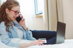 Szczęśliwy młody bizneswoman używa pastylka komputer osobistego w pokoju hotelowym Z kredytową kartą online zakupy Obrazy Stock