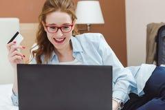 Szczęśliwy młody bizneswoman używa pastylka komputer osobistego w pokoju hotelowym Z kredytową kartą online zakupy Zdjęcia Royalty Free