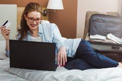 Szczęśliwy młody bizneswoman używa pastylka komputer osobistego w pokoju hotelowym Z kredytową kartą online zakupy Zdjęcie Royalty Free