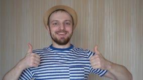 Szczęśliwy młody brodaty mężczyzna w kapeluszu i pasiastej koszulce daje aprobatom zbiory wideo