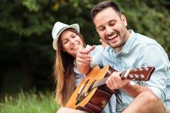 Szczęśliwy młody człowiek bawić się gitarę jego piękna dziewczyna obraz royalty free