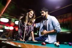 Szczęśliwy młody człowiek bawić się snooker z jego dziewczyną szcz??liwy kocha? pary zdjęcie royalty free