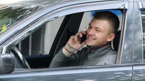 Szczęśliwy młody człowiek ciągnie na drodze opowiadać na jego telefonie komórkowym Biznesmen w samochodowym mówieniu na smartphon Obrazy Royalty Free