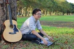 Szczęśliwy młody człowiek jest relaksujący z gitarą akustyczną w miasta lata parku i laptopem obraz stock