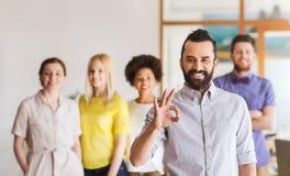Szczęśliwy młody człowiek nad kreatywnie drużyną w biurze Zdjęcia Stock