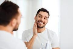 Szczęśliwy młody człowiek patrzeje odzwierciedlać w domu łazienkę Zdjęcie Royalty Free
