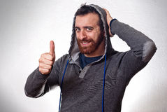 Szczęśliwy młody człowiek pokazuje kciuk up podpisuje Fotografia Stock
