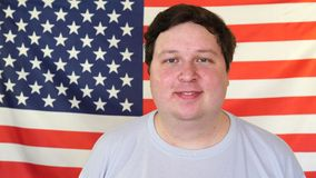 Szczęśliwy młody człowiek pozuje dla portreta przed flagą amerykańską zbiory