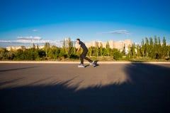 Szczęśliwy młody człowiek rollerblading w miasto parku przy zmierzchem Fotografia Stock