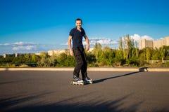 Szczęśliwy młody człowiek rollerblading w miasto parku przy zmierzchem Fotografia Royalty Free