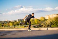 Szczęśliwy młody człowiek rollerblading w miasto parku przy zmierzchem Obraz Stock