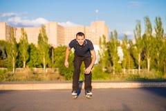 Szczęśliwy młody człowiek rollerblading w miasto parku przy zmierzchem Zdjęcie Royalty Free