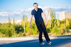 Szczęśliwy młody człowiek rollerblading w miasto parku przy zmierzchem Obrazy Royalty Free
