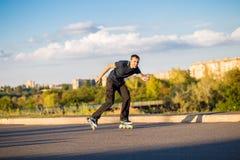 Szczęśliwy młody człowiek rollerblading w miasto parku przy zmierzchem Zdjęcia Stock
