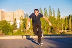 Szczęśliwy młody człowiek rollerblading w miasto parku przy zmierzchem Obrazy Stock
