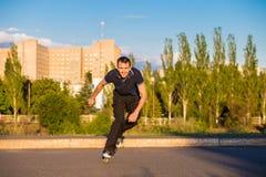 Szczęśliwy młody człowiek rollerblading w miasto parku przy zmierzchem Zdjęcia Royalty Free