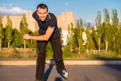 Szczęśliwy młody człowiek rollerblading w miasto parku przy zmierzchem Obraz Royalty Free