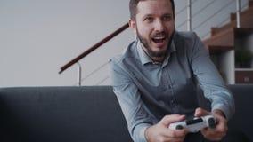 Szczęśliwy młody człowiek siedzi na kanapie i cieszy się nowego gra wideo mienia joysticka kontrolera zbiory