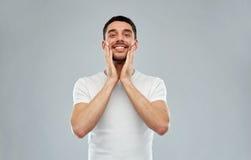 Szczęśliwy młody człowiek stosuje aftershave twarz Zdjęcie Stock