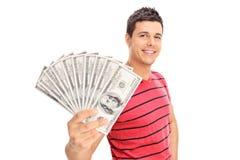 Szczęśliwy młody człowiek trzyma stos gotówka Fotografia Stock