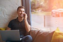 Szczęśliwy młody człowiek używa laptop i telefon komórkowego na leżance Zdjęcie Stock