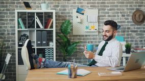 Szczęśliwy młody człowiek używa smartphone i pijący kawę w miejsce pracy zbiory