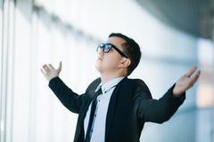 Szczęśliwy młody człowiek w formalwear odświętności, gestykulujący, utrzymujący zbroi nastroszonego positivity w panoramicznym na zdjęcia stock