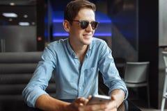 Szczęśliwy młody człowiek w szkłach, z telefonem w ręce, siedzi w kawiarni, stosownej dla reklamować, teksta przyczepienie zdjęcie stock