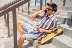 Szczęśliwy młody człowiek z łyżwowym używa smartphone Obrazy Royalty Free