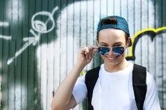 Szczęśliwy młody człowiek z szkłami blisko ściany zdjęcia stock