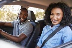 Szczęśliwy młody czarny pary jeżdżenie w samochodzie ono uśmiecha się kamera zdjęcie stock