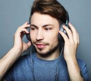 Szczęśliwy młody elegancki mężczyzna przystosowywa jego hełmofon reklamy uśmiechniętego wh obrazy stock