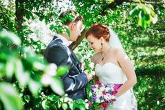 Szczęśliwy młody mąż i żona, w kwiatach, patrzeją bukiet Obrazy Stock