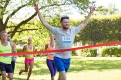 Szczęśliwy młody męski biegacza wygranie na biegowym konu Zdjęcia Royalty Free