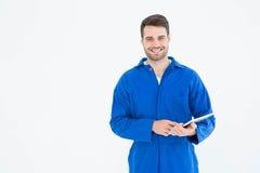 Szczęśliwy młody męski mechanik używa cyfrową pastylkę Obraz Royalty Free