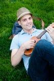 Młody męski uczeń z ukulele Obrazy Royalty Free