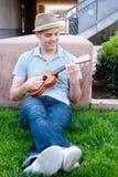 Młody męski uczeń z ukulele Zdjęcia Royalty Free