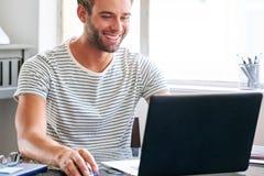 Szczęśliwy młody męski uczeń ono uśmiecha się podczas gdy sadzający za jego laptopem Zdjęcia Stock
