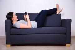 Szczęśliwy młody piękny kobiety lying on the beach na kanapie i używać mądrze telefon Fotografia Stock