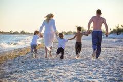 Szczęśliwy młody rodzinny bieg na plaży przed zmierzchem zdjęcia stock