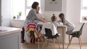 Szczęśliwy młody rodzinny bierze śniadanie w białej kuchni z małymi dziećmi wpólnie w domu Łasowanie Bliny zbiory wideo
