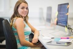 Szczęśliwy młody studencki ono uśmiecha się przy kamerą w komputerowym pokoju Fotografia Royalty Free